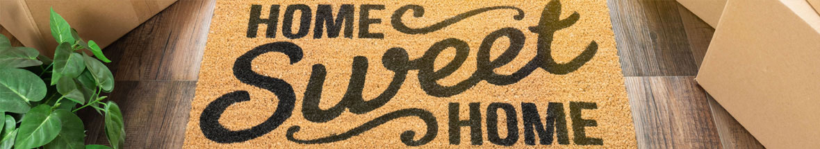 doormat with 'Home Sweet Home' surrounded by packing boxes