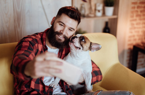 bearded man taking a selfie with his dog
