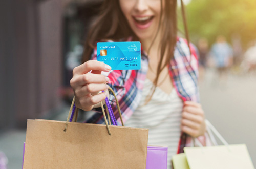 smiling woman holding credit cards and shopping packages